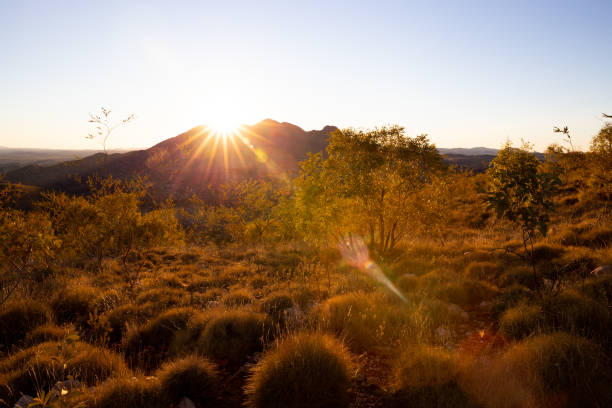 Late afternoon sun shines brightly across the top of a desert mountain in Australian Outback stock photo