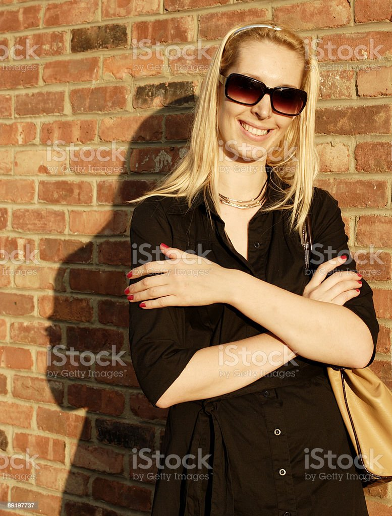 Late Afternoon Woman against Brick Wall royalty free stockfoto