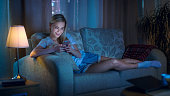 Late At Night Beautiful Woman Lying on Her Sofa in the Living Room, Using Her Smartphone and Smiling.