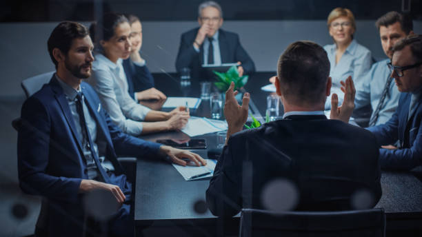 Late at Night In the Corporate Office Meeting Room: At Conference Table Executive Director Talks to a Board of Directors, Investors and Business Associates. Over the Shoulder Shot. stock photo