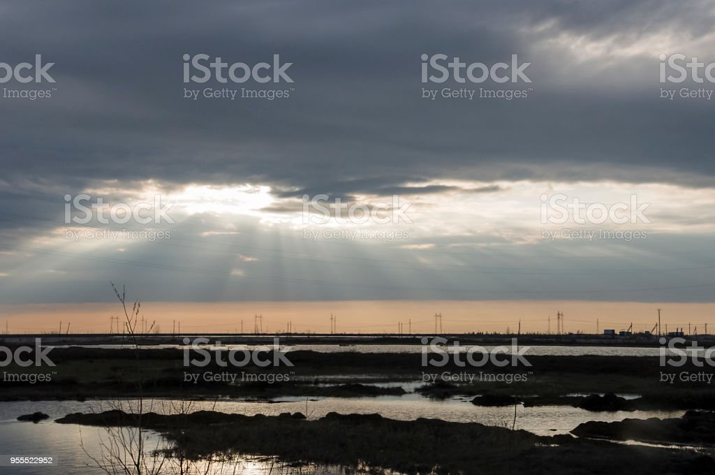 Late at night. Sundown and sunrises. River running across the field with reflections in the water. Evening  with dark blue, violets colors in the sky stock photo