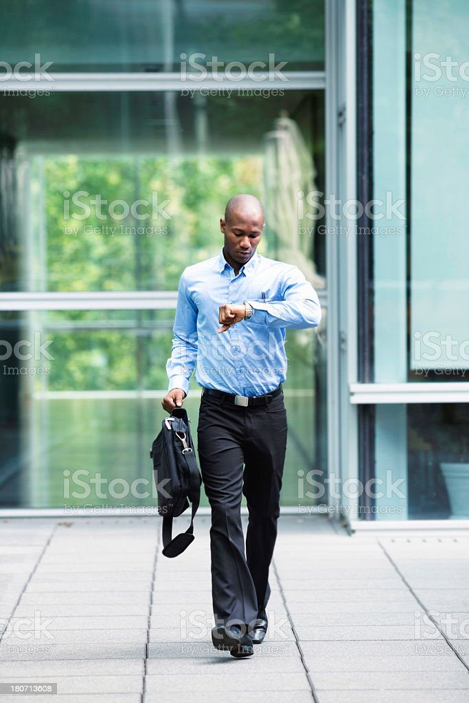 Late businessman leaving his office looking at watch stock photo