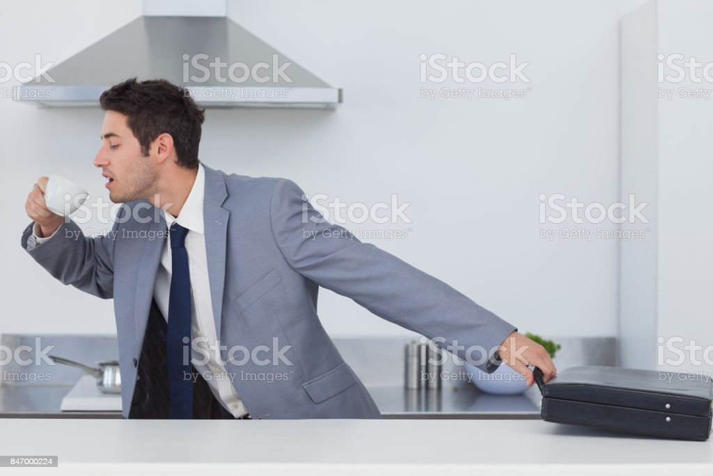 A late businessman taking his briefcase stock photo