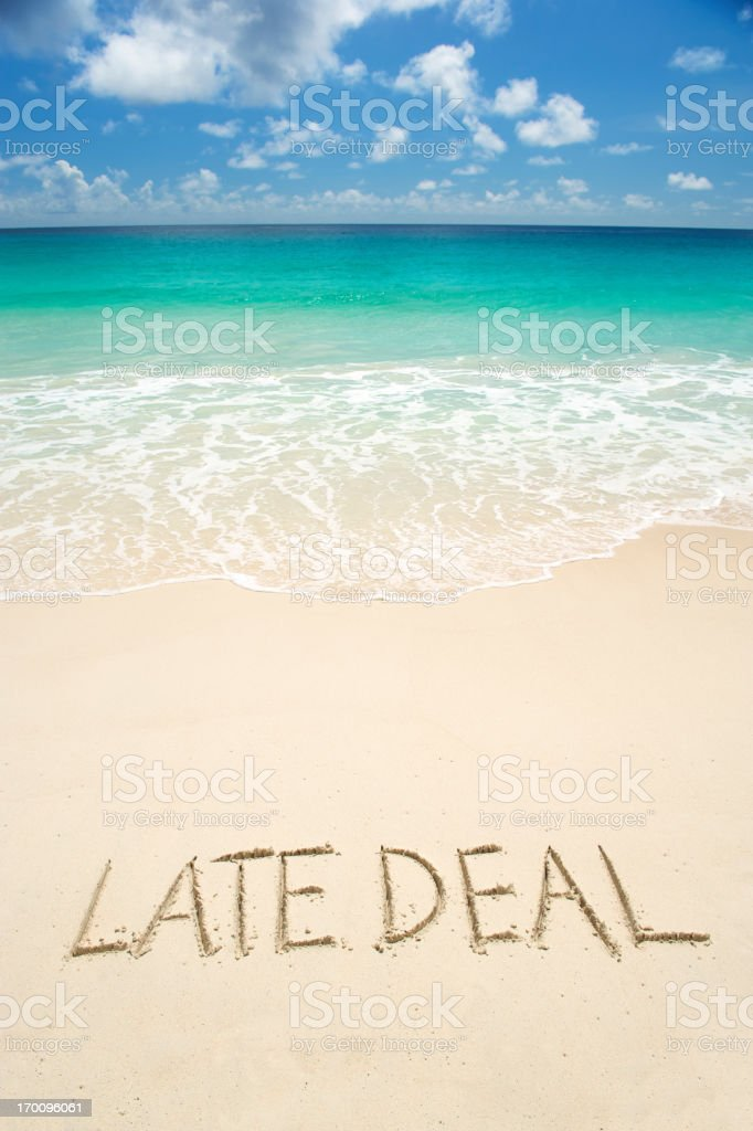 Late Deal Message in Sand on Bright Tropical Beach stock photo