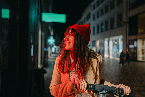 Photo of a young woman riding an e-scooter late at night, in a downtown of a city; illuminated by the neon street lights.