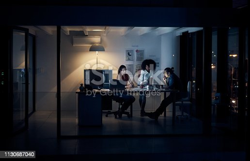 Full length shot of three young creative businesspeople meeting in their office at night