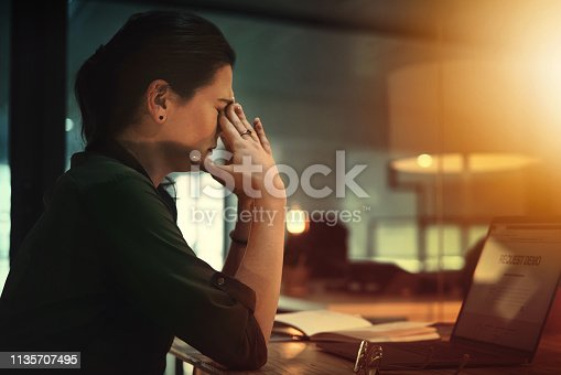 Shot of a young businesswoman looking stressed out while working on a laptop in an office at night