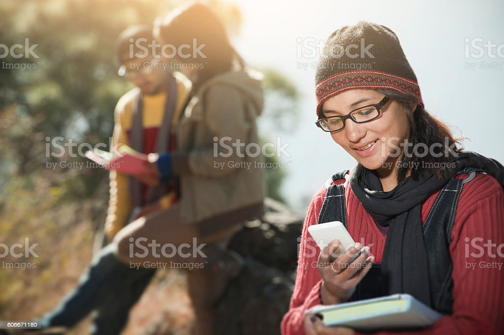 Late teen girl student using smart phone holding a book. stock photo