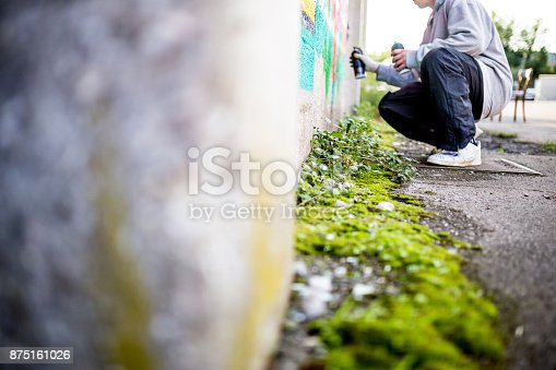 Late Teen Graffiti Artist Drawing Graffiti on Wall.
