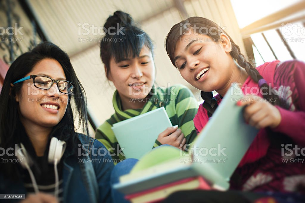 Outdoor low angle image of three late teen happy Asian girl students...