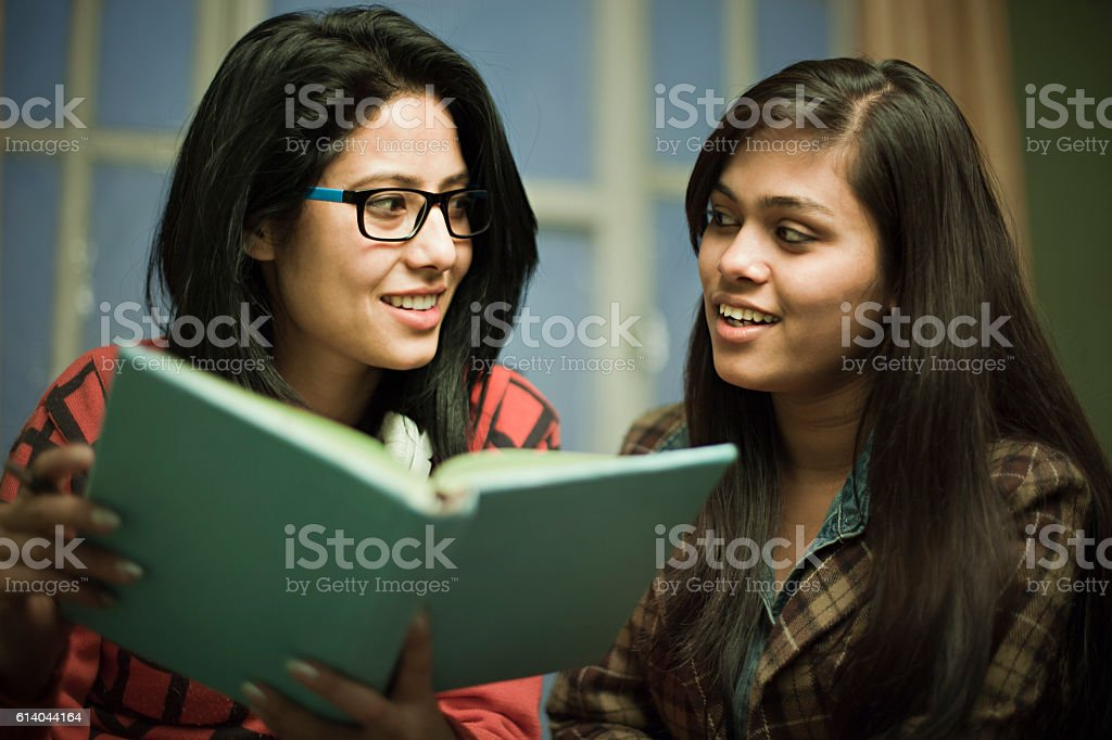 Late teen happy girl students studying together. stock photo