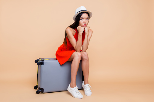 Late train long lost city hotel problem people person concept. Full length body size photo of depressed stressed disappointed upset face lady sitting heavy hard big suitcase isolated beige background