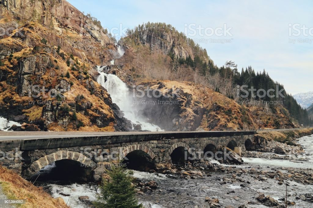 Latefossen Waterfall Odda Norway with the stone road bridge across in spring April season. Latefoss is a powerful, twin waterfall.Latefoss is one of the famous sightseeing waterfall. stock photo