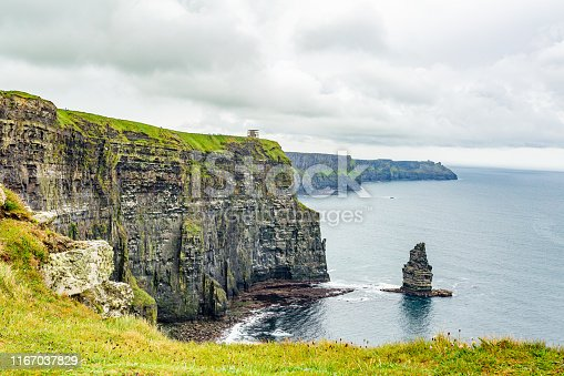Lateral view of the Cliffs of Moher and the Branaunmore sea stack, geosites and geopark, Wild Atlantic Way, wonderful cloudy spring day in County Clare in Ireland