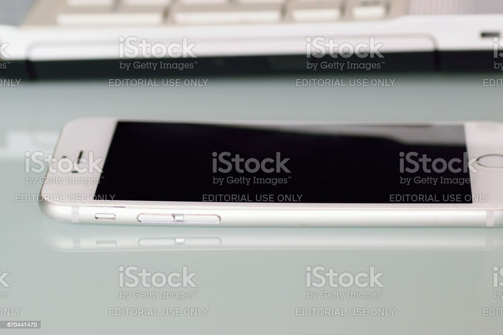 Latest iPhone on desk in horizontal frame with blurred laptop PC keyboard stock photo
