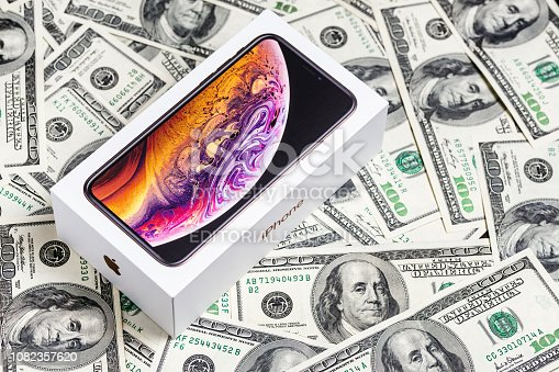 istock Latest Iphone XS in unopened box on US dollar banknotes background. 1082357620