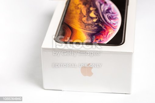 istock Latest Iphone XS in unopened box on white table. Newest Apple smartphone on white branded box in mobile store. Modern gadget with dual camera and OLED screen for sale 1055264940