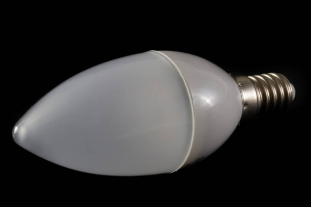 Latest modern LED light bulb in candle shape on black background- modern eco energy-saving technology stock photo
