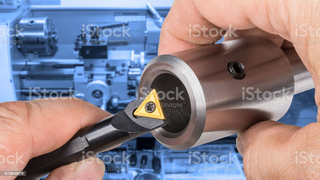 Lathe cutter for machining holes and workpiece on blue blurred background stock photo