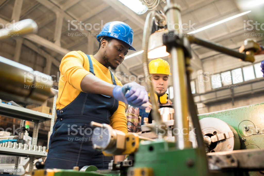 Lathe Operators Concentrated on Work Multi-ethnic team of workers wearing overalls and protective helmets using lathe in order to machine workpiece, interior of spacious production department on background Adult Stock Photo