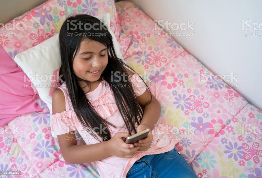 Latin american 8 year old chatting on a smartphone looking very happy while lying down on her bed stock photo