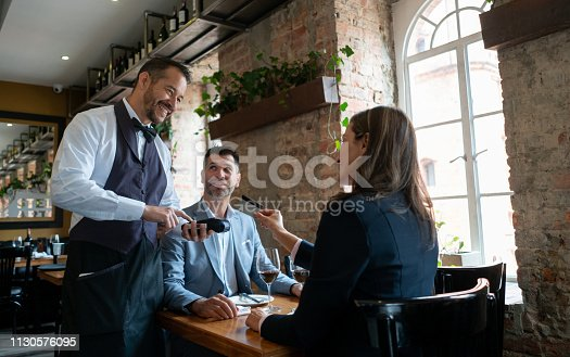 Latin american adult couple at a restauyrant on a date and woman paying with a credit card to waiter all smiling