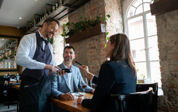 latinamerikansk vuxen par på en restauyrant på ett datum och kvinna som betalar med ett kreditkort till servitören - middle aged man dating bildbanksfoton och bilder