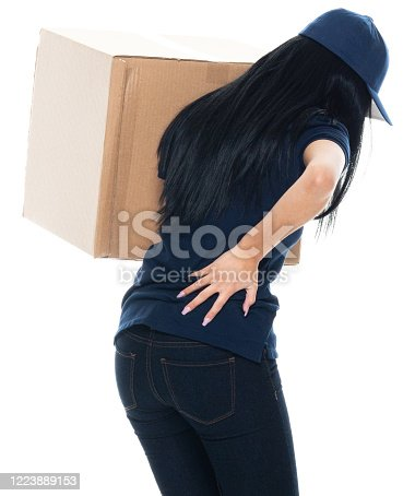 istock Latin american and hispanic ethnicity female manual worker standing in front of white background wearing polo shirt and holding package 1223889153