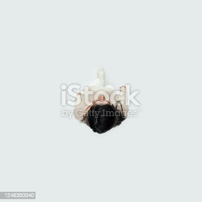 Directly above view of aged 20-29 years old who is beautiful with black hair latin american and hispanic ethnicity female walking in front of white background wearing warm clothing who is laughing