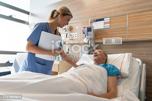 Latin american beautiful doctor checking on senior patient lying down on hospital bed talking to him both smiling very happy