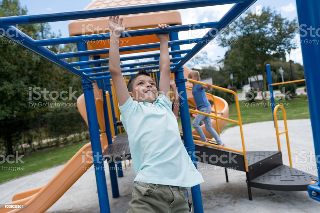 Rapaz latino-americano se divertindo nas barras de macaco no parque infantil - foto de acervo