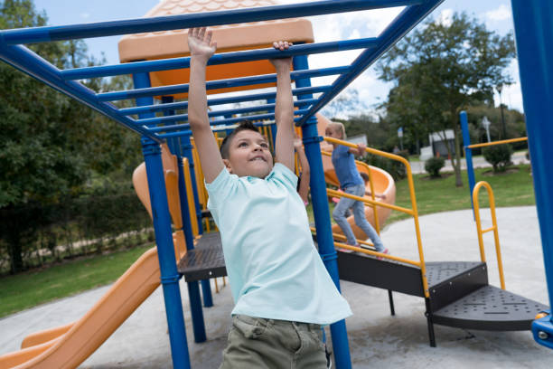 Latin american boy having fun on the monkey bars at the playground stock photo