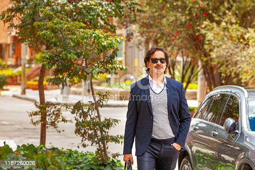 A latin american business manager is seen walking down a city street. It is a bright sunny day and he has sunglasses on. Dressed in business casual clothes, he has a bag in one hand and the other hand is in his trouser pocket.