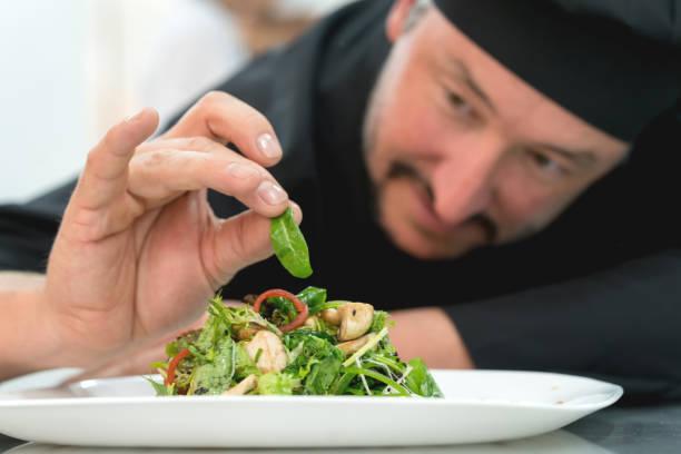 lateinamerikanischen chef hinzufügen die veredelung berührt, um seinen salat - erdnusssalatdressings stock-fotos und bilder