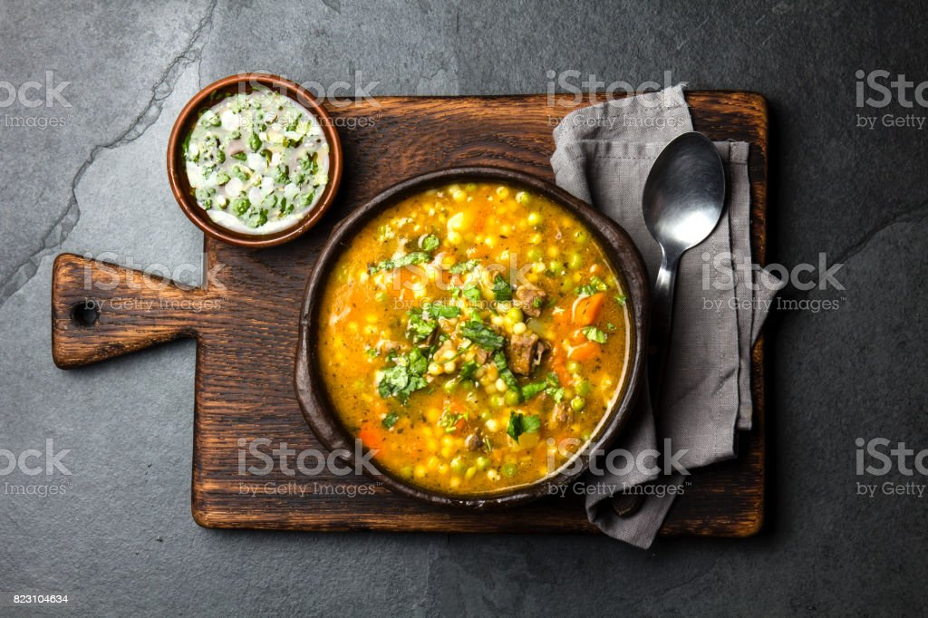 Latin American chilean food. Traditional chilean carbonara. Stewed beef with pumpkin, potatoes and vegetables in clay bowl. Top view. stock photo