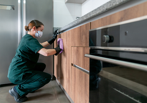 Latin American cleaner wearing a facemask while cleaning the kitchen