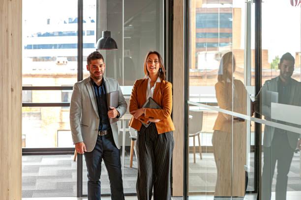 Lateinamerikanische Kollegen, ein junger Mann und eine junge Frau, bei der Arbeit im Büro; Sie zeigt ihm einige Daten auf ihrem digitalen Tablet. Bildaufnahme im natürlichen Licht; Horizontales Format. – Foto