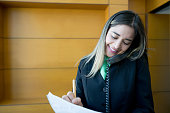 Latin american concierge working at the front desk talking on the phone smiling very happy