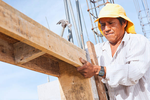 Latin American construction site with worker A close-up of an Latin American construction worker on site in Central America.  A male construction worker works on a concrete form on a building site in Costa Rica.  many of the workers on these sites are migrant Nicaraguans who work for a few dollars a day and travel home to Nicaragua frequently to remit money and see family. migrant worker stock pictures, royalty-free photos & images