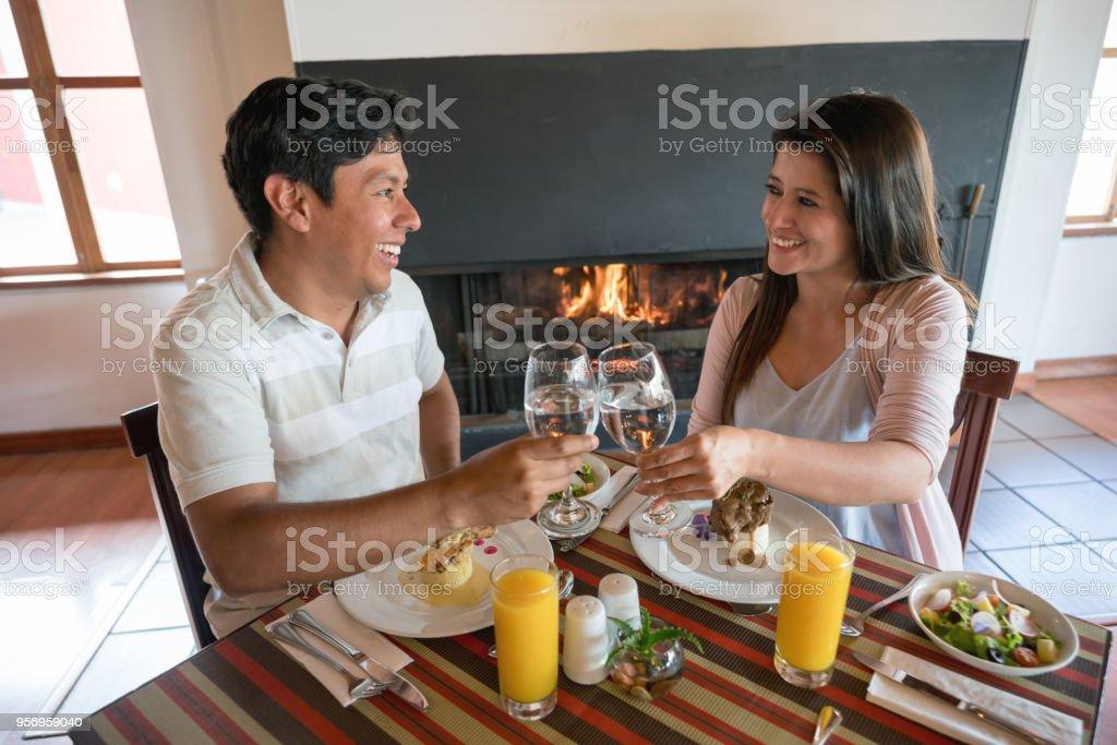 Casal latino-americano em um restaurante para comemorar seu aniversário fazendo um brinde - foto de acervo