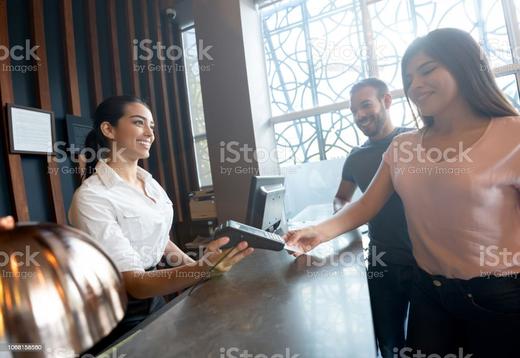 Latin american couple checkin out from hotel paying with credit card...