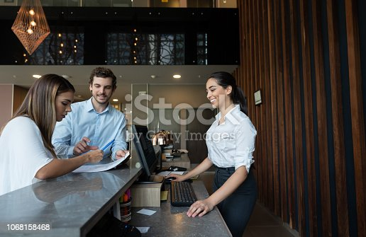 istock Latin american couple doing check in at hotel and friendly receptionist smiling 1068158468