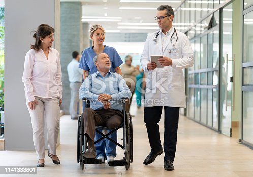 istock Latin american doctor talking to patient in wheelchair and partner while nurse is standing behind all smiling 1141333801
