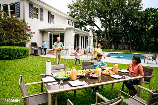 Multi-generation Hispanic family gathering at a backyard table for a summertime cookout in Miami, Florida.