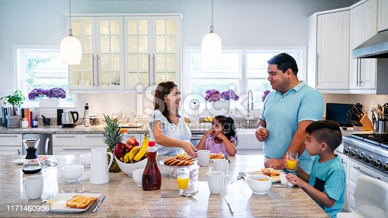 Mature Hispanic parents enjoying breakfast with their young son and daughter at a granite island in their spacious kitchen.