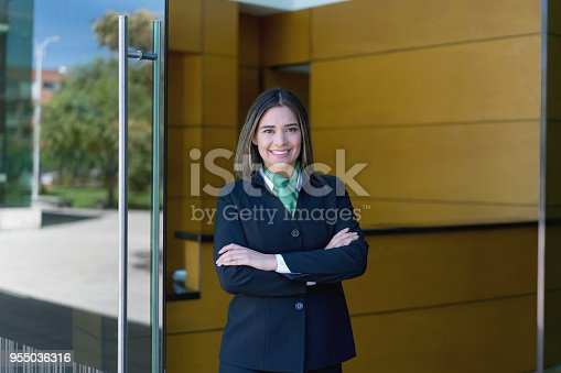 Latin american female hotel manager standing at the entrance with arms crossed looking at camera very happy and smiling