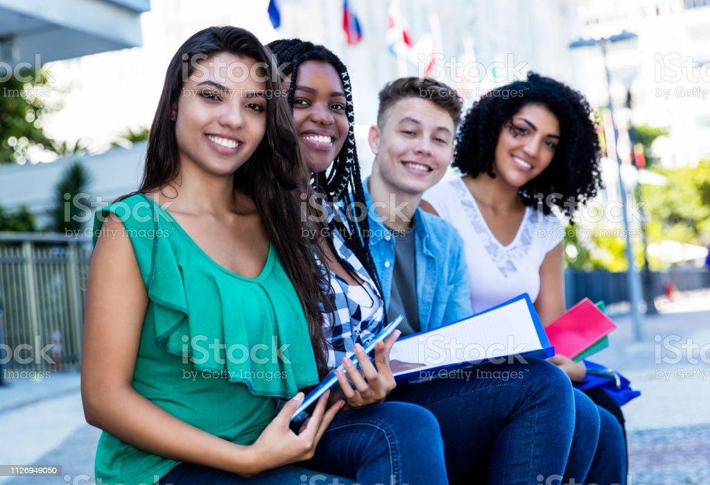 Estudiante femenino de América Latina con el grupo de estudiantes internacionales al aire libre en el verano en la ciudad - foto de stock