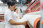 Latin american females ironing sheets with an industrial iron looking focused