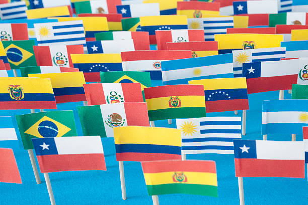 Latin American flags Lots of small handmade flags of latin american countries over blue background latin america stock pictures, royalty-free photos & images
