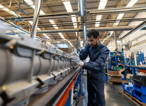 Latin american focused young man working at a manufacturing water pump factory - Industrial concepts
